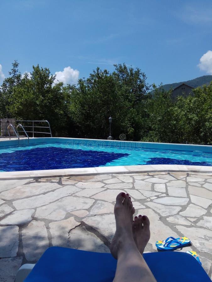 Rust op een de zomerdag door de pool stock foto
