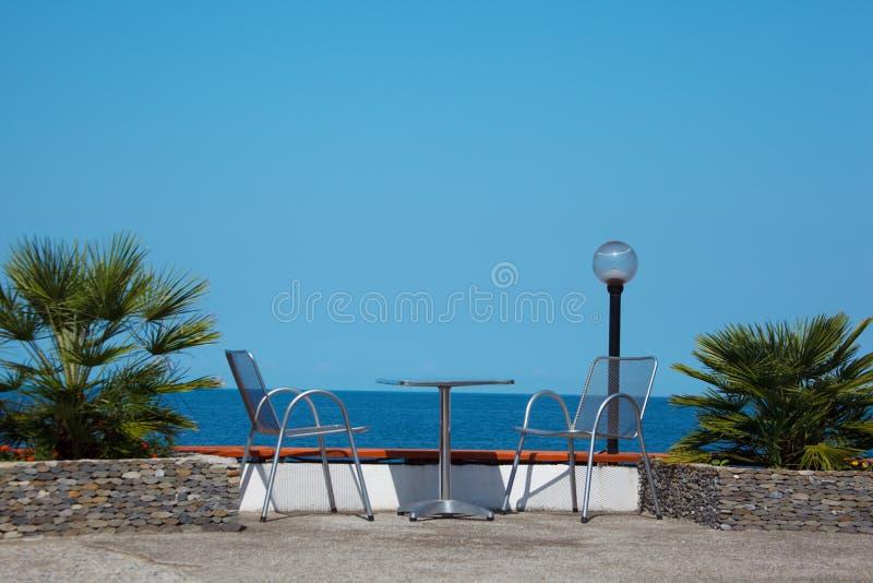 Rust op kust. Lijst en stoelen op strand stock fotografie