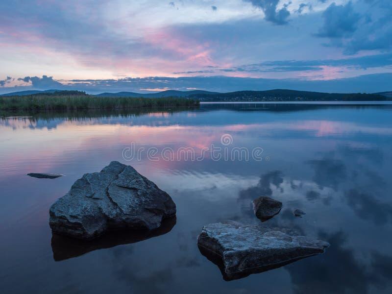 Rust, sereniteit, meditatieconcept Zonsondergang op het meer, stenen in het water in de voorgrond, stil water, wolkenloze hemel stock foto's