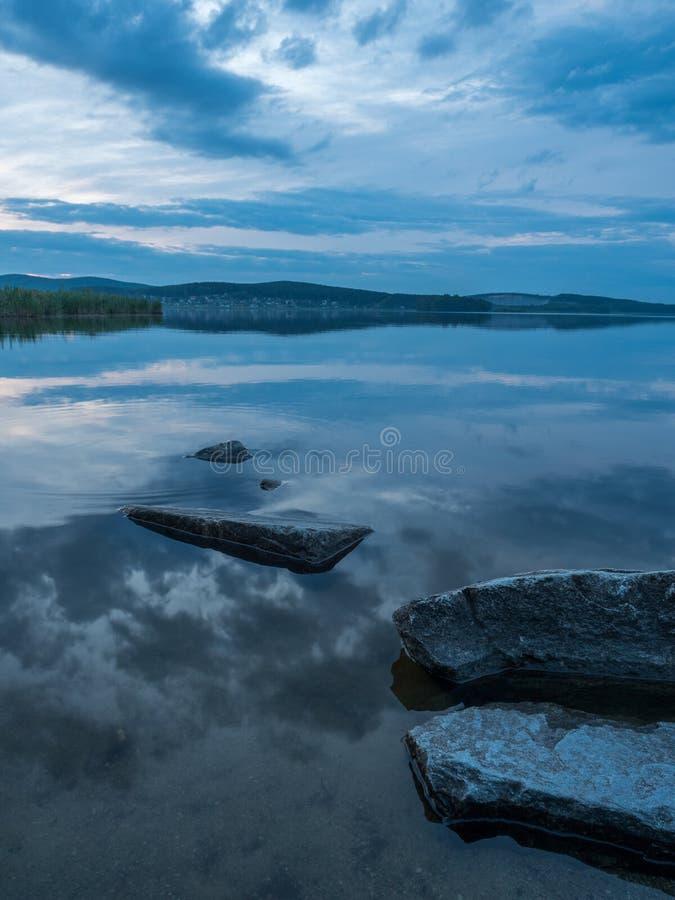 Rust, sereniteit, meditatieconcept Zonsondergang op het meer, stenen in het water in de voorgrond, stil water, wolkenloze hemel royalty-vrije stock fotografie