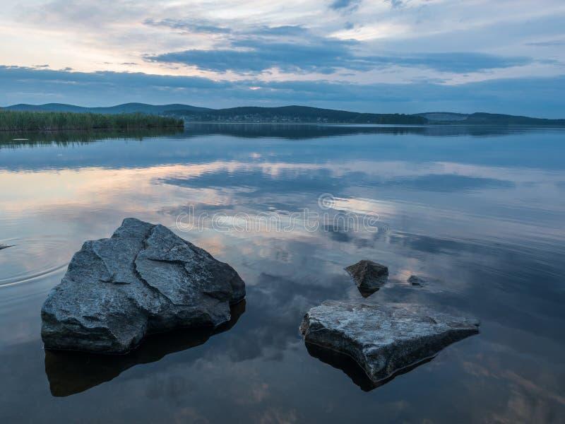 Rust, sereniteit, meditatieconcept Zonsondergang op het meer, stenen in het water in de voorgrond, stil water, wolkenloze hemel royalty-vrije stock foto