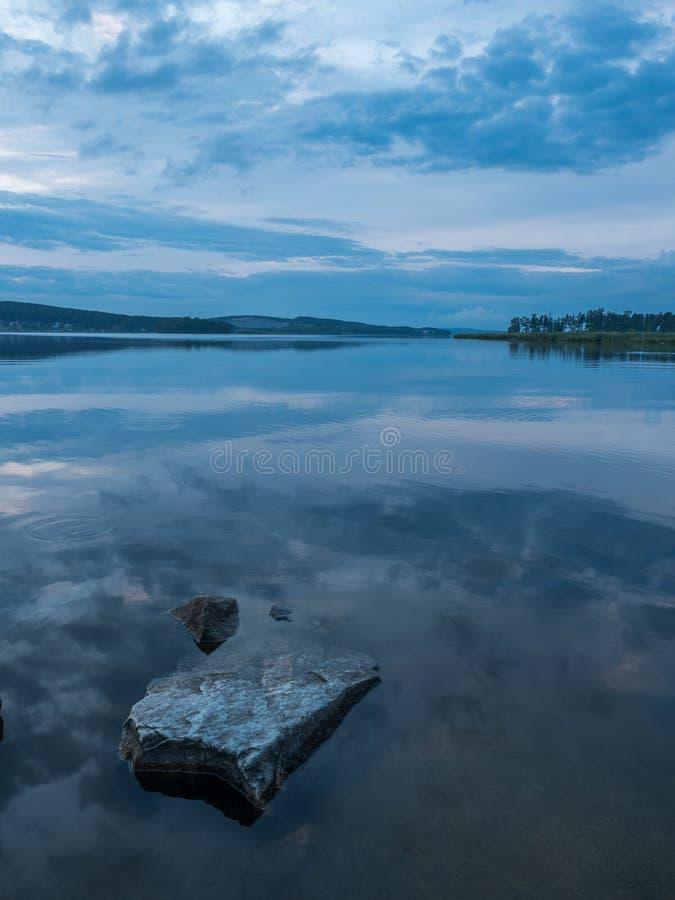 Rust, sereniteit, meditatieconcept Zonsondergang op het meer, stenen in het water in de voorgrond, stil water, wolkenloze hemel stock foto