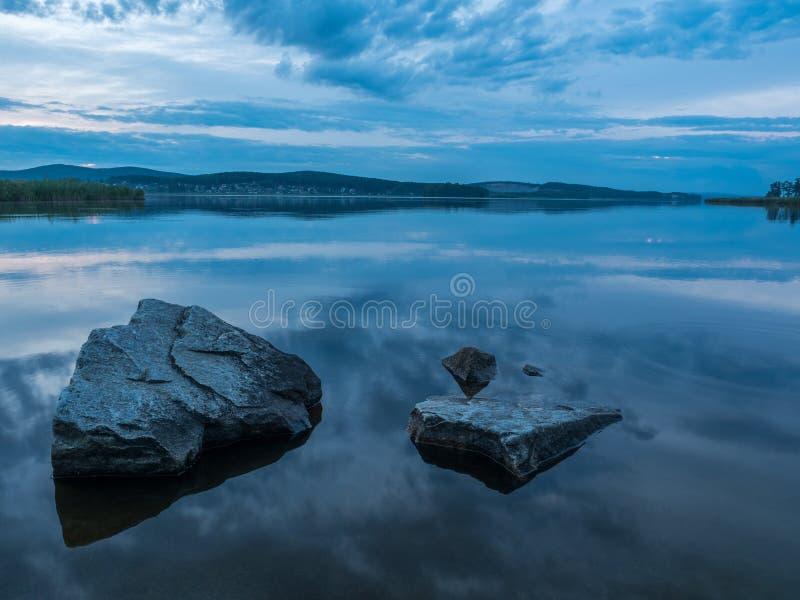 Rust, sereniteit, meditatieconcept Zonsondergang op het meer, stenen in het water in de voorgrond, stil water, wolkenloze hemel stock afbeelding