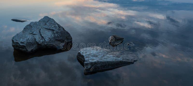 Rust, sereniteit, meditatieconcept Zonsondergang op het meer, stenen in het water in de voorgrond, stil water, wolkenloze hemel royalty-vrije stock foto's