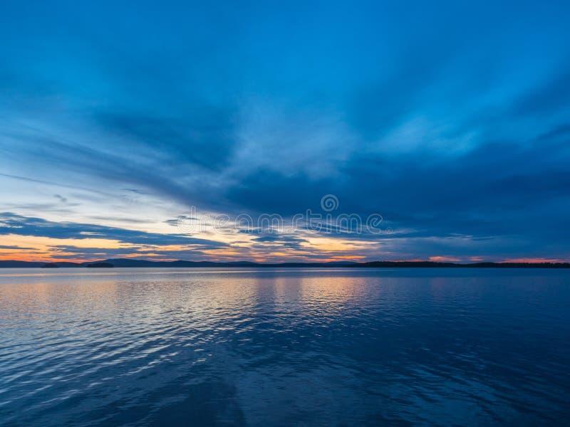 Rust, sereniteit, meditatieconcept Zonsondergang op het meer, stil water, wolkenloze hemel stock afbeelding