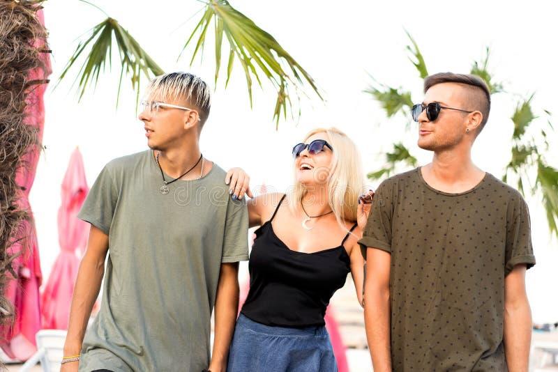 Rust van het drie vrienden de vrolijke bedrijf op een tropisch strand en drin stock foto