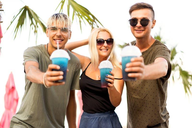 Rust van het drie vrienden de vrolijke bedrijf op een tropisch strand en drin stock afbeeldingen