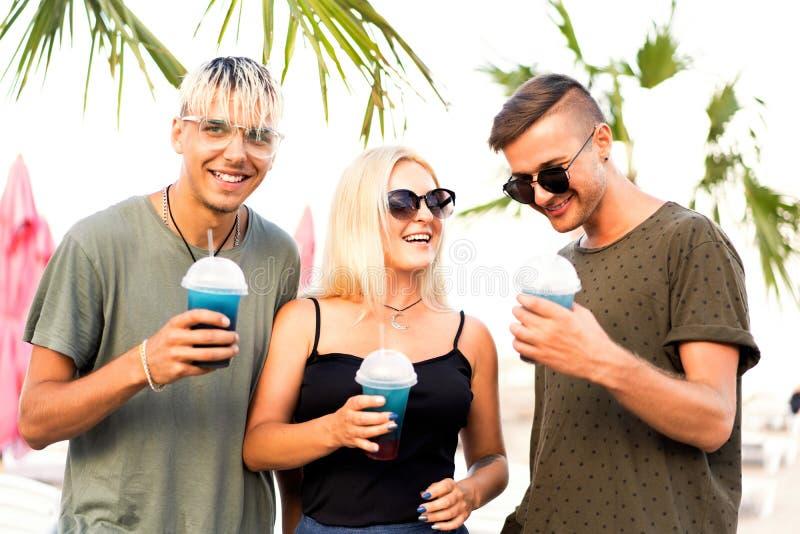 Rust van het drie vrienden de vrolijke bedrijf op een tropisch strand en drin royalty-vrije stock afbeelding