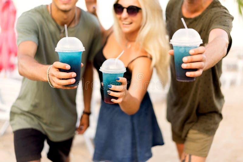 Rust van het drie vrienden de vrolijke bedrijf op een tropisch strand en drin royalty-vrije stock foto