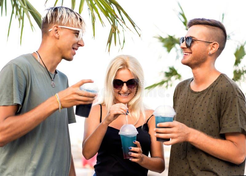 Rust van het drie vrienden drinkt de vrolijke bedrijf op een tropisch strand en cocktails, zeer, tijdschriftconcept stock afbeeldingen