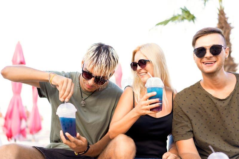 Rust van het drie vrienden drinkt de vrolijke bedrijf op een tropisch strand en cocktails, zeer, tijdschriftconcept stock fotografie