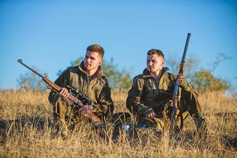 Rust voor echt mensenconcept Het bespreken van vangst Jagers die met geweren in aardmilieu ontspannen De jagersvriend geniet van stock fotografie