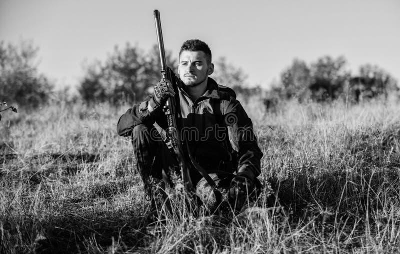 Rust voor echt mensenconcept Jager met geweer het ontspannen in aardmilieu Vermoeid maar tevreden Eind van seizoen jager royalty-vrije stock foto's