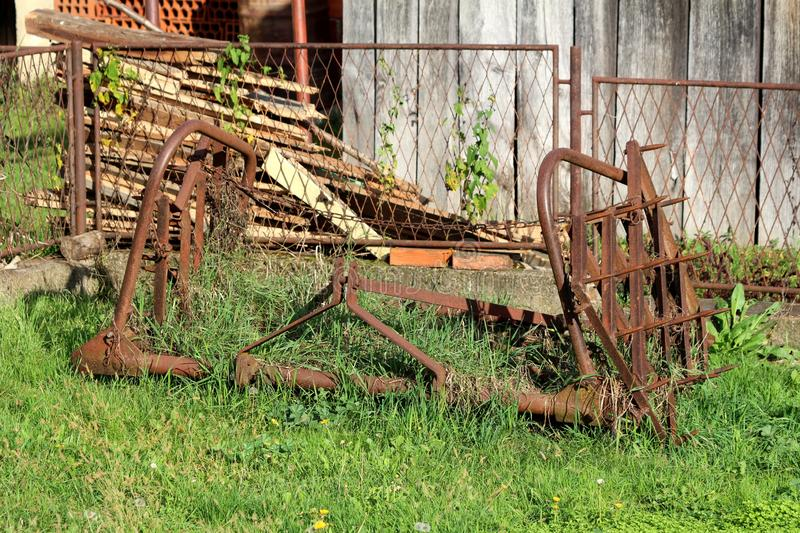 Rusted abandoned vintage agricultural farming equipment used to work with tractors on soil left in high grass in front of metal. Rusted fence and old barn on royalty free stock images