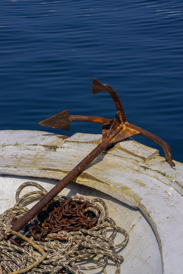Rusted anchor attached to the rope on the boat portrait. Image royalty free stock photos