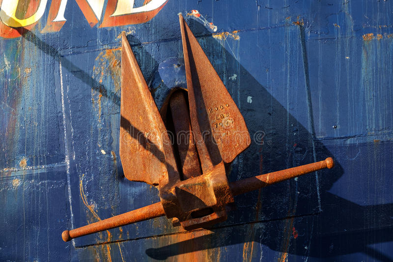 Rusted anchor on boat. A rusted red steel anchor against the blue steel hull of a commercial fishing boat at Fishermens Terminal in Seattle, Washington royalty free stock photo