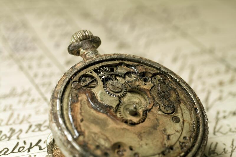 Rusted antique pocket watch on an old notebook stock image