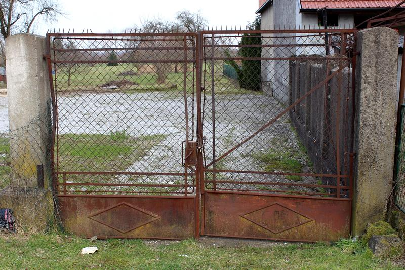 Rusted backyard metal locked gates royalty free stock photography