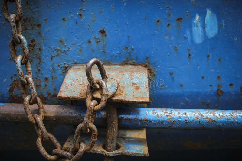 Rusted Chain on rusty dumpster. Rusted chains on a rusted metal dumpster represents something distressed, worn out, weighted, or bound to something stock image