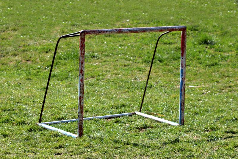 Rusted heavily used old metal goal post surrounded with uncut grass waiting for restoration and painting on local playground stock images