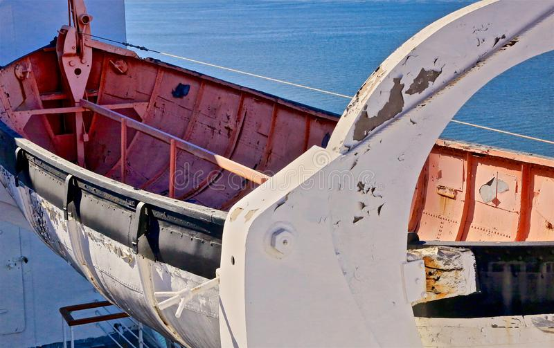 Dinghy red white boat Queen Mary Ship California. Rusted historic dinghy boat hanging on side of Queen Mary Ship in Long Beach California stock photo