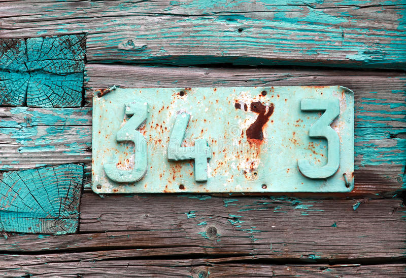 Rusted house number on grunge green wall royalty free stock image