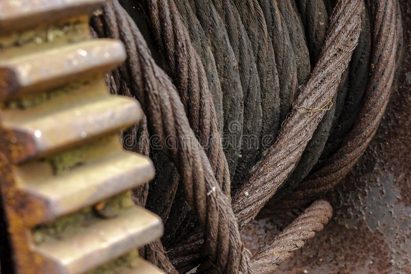 Rusted iron cable on a giant industrial spool. A rusty iron cable on a giant spool. Some grease is visible on the deeper parts of the spool. On the left side a stock photo