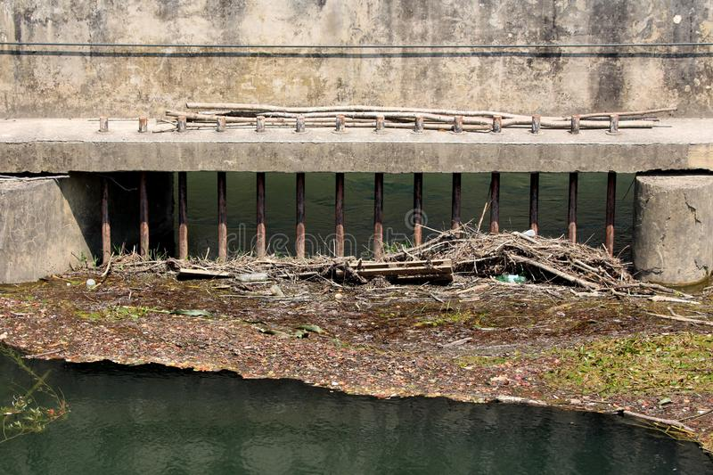 Rusted metal bars mounted on concrete dam wall set to prevent garbage floating on incoming water. Rusted metal bars mounted on hard concrete dam wall set to stock photography