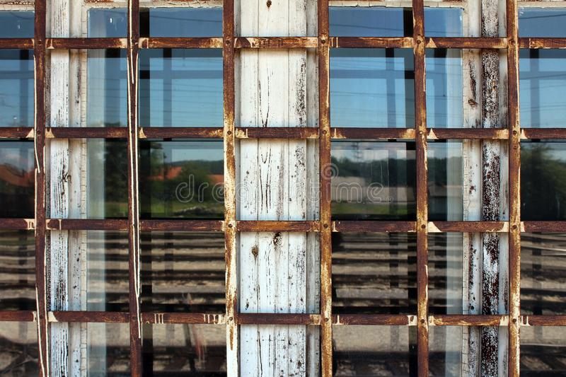 Rusted metal bars in shape of net mounted on old dilapidated white wooden window frame. With windows reflecting houses, trees and clear blue sky in background royalty free stock photography