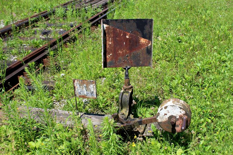 Rusted metal black and white railway switch mechanism with metal sign mounted on wooden board. Next to railway track surrounded with overgrown uncut green grass royalty free stock image