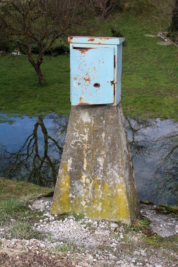 Rusted metal electrical junction box mounted on concrete pole. Rusted metal electrical junction box with open door mounted on concrete pole and surrounded with royalty free stock photos