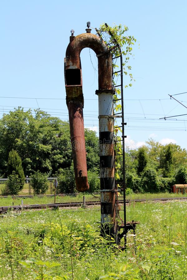 Rusted metal railway white and black water pump with rusted and overgrown metal ladder mounted on side. Surrounded with high uncut grass with trees and clear stock photography