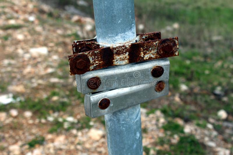 Metal round post mount brackets mounted on grey post. Rusted and new metal round post mount brackets for holding signs mounted on grey metal post with sand and stock photo