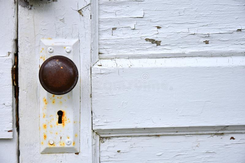 Rusted Old Doorknob and Keyhole. A close up image of a rusted old doorknob and keyhole on a white door stock image