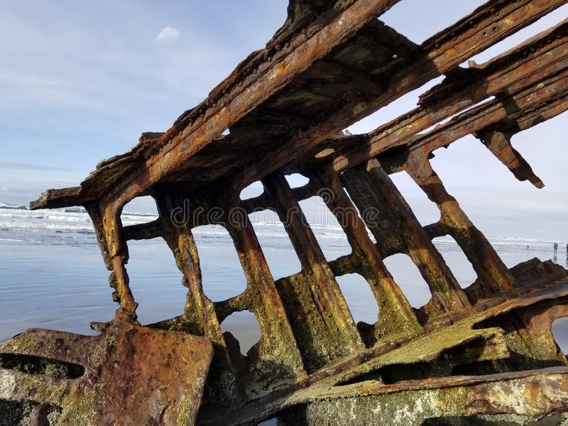Rusted shipwreck on beach stock images