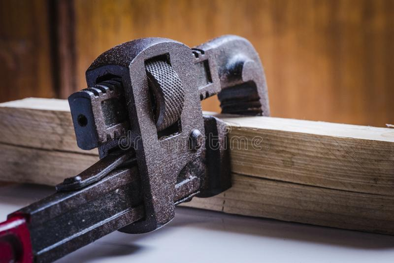 Stained rusted pipe Wrench handtool. Rusted, stained pipe wrench hand tool clamped with a wooden block stock images