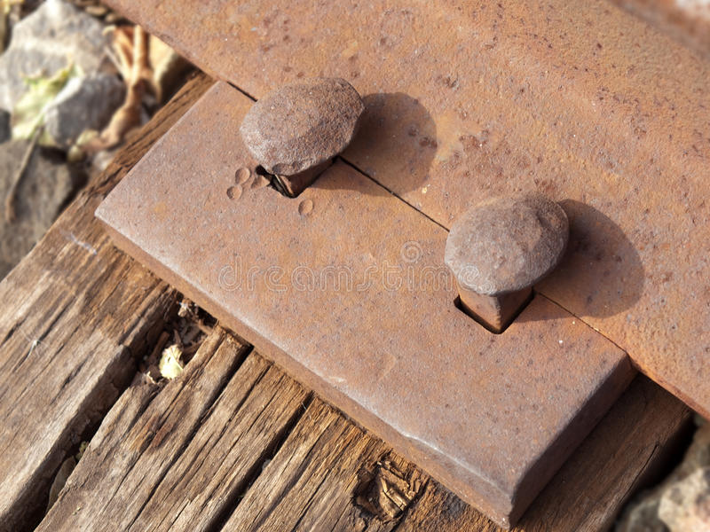 Rusted Train Rail. Closeup of the heads of rusted train rail spikes holding rail in place with some of the wooden tie showing stock images
