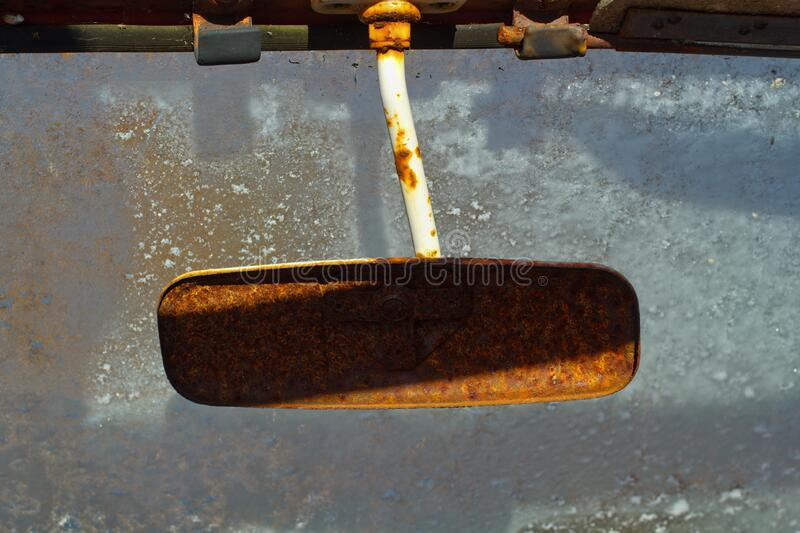 Rusted Vehicle Mirror. Old and rusted vehicle rear view mirror and icy windshield stock photo
