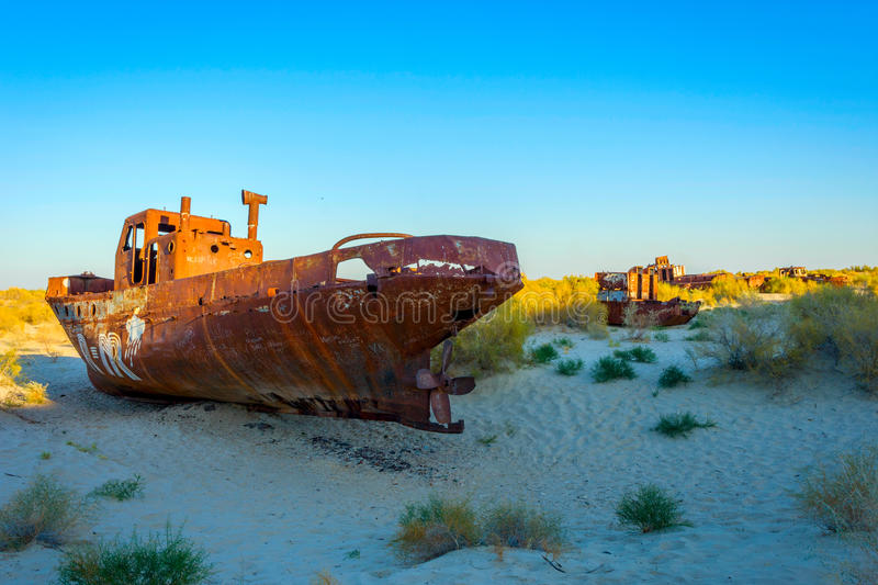 Rusted vessel in the ship cemetery, Uzbekistan. Old ships in the desert `ship cemetery` the consequence of Aral sea disaster, Muynak, Uzbekistan royalty free stock photography