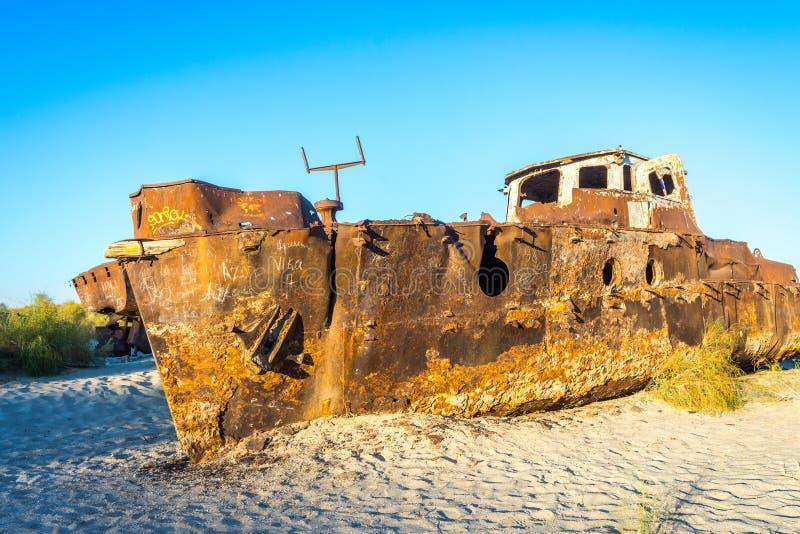 Rusted vessel in the ship cemetery, Uzbekistan. Old ships in the desert `ship cemetery` the consequence of Aral sea disaster, Muynak, Uzbekistan royalty free stock image