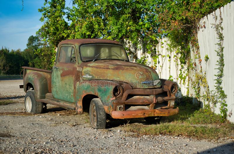 Rusted vintage Chevrolet pickup truck parked by a white fence. royalty free stock image