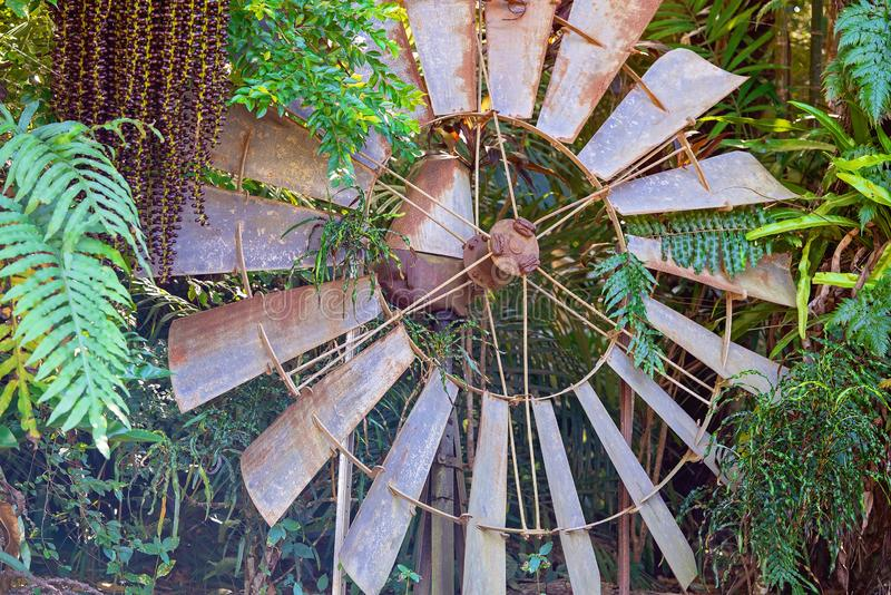 Rusted Vintage Windmill Abandoned In Bushland. Rusted old windmill blades left abandoned amongst trees in dense bushland royalty free stock image