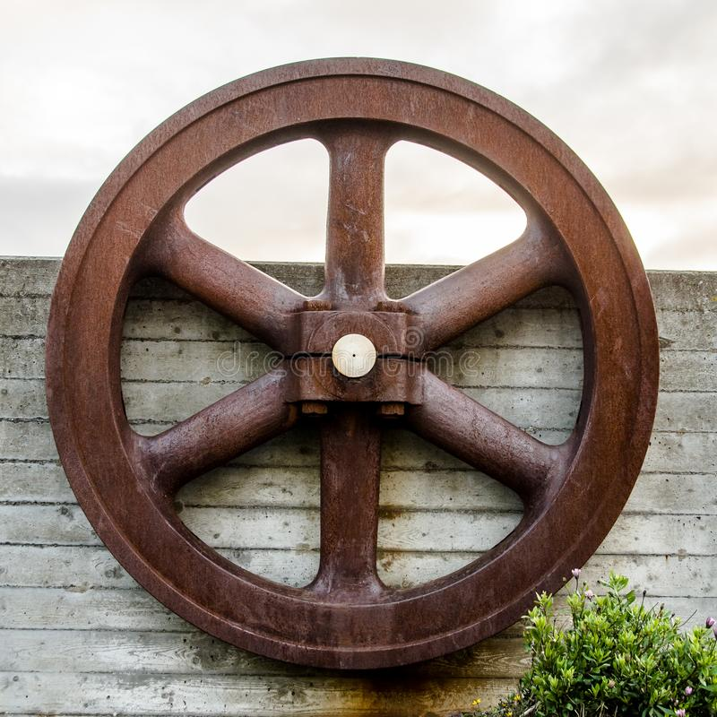 Rusted wheel on a wall. Antique rusted wheel on a garden wall, garden decor stock image