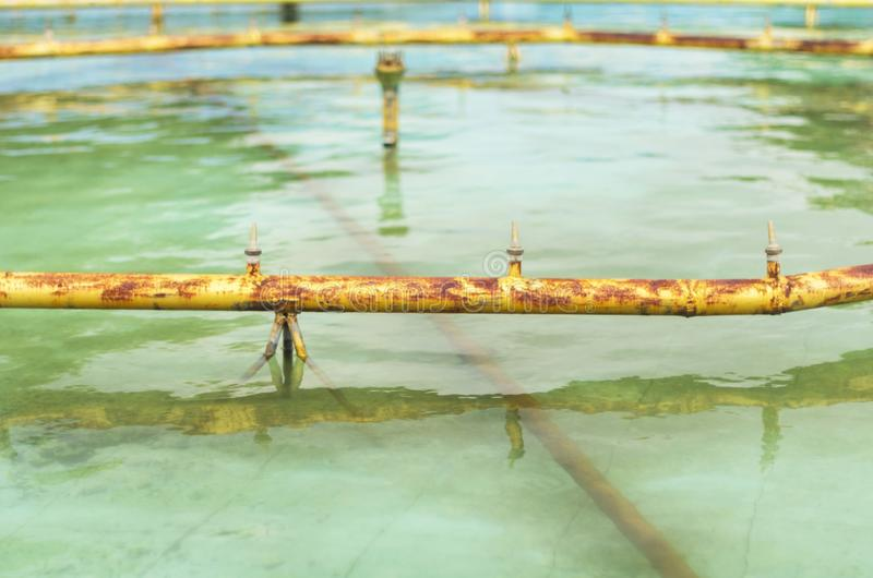 Rusted yellow pipes and water jets of a fountain drained for maintenance or servicing on a summer day.  stock image