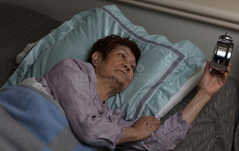 Rusteloze hogere vrouw die bij wekker tijdens nacht schitteren wh stock fotografie