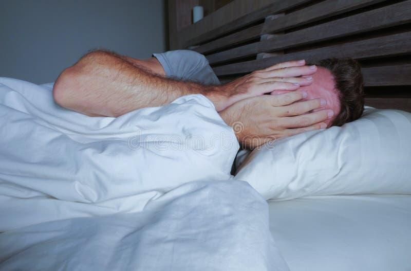 Rusteloze ongerust gemaakte jonge aantrekkelijke mens wakker bij nacht die op bed slapeloos behandelend gezicht liggen met handen stock foto