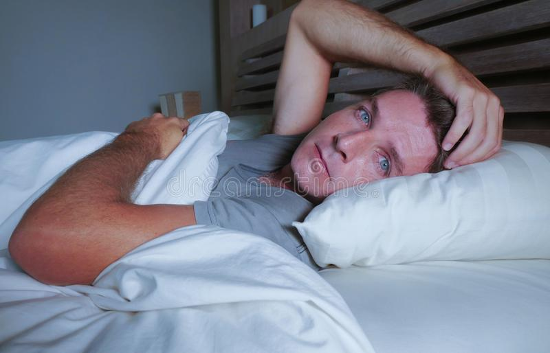 Rusteloze ongerust gemaakte jonge aantrekkelijke mens wakker bij nacht die op bed slapeloos met wijd geopende ogen liggen lijdend stock foto