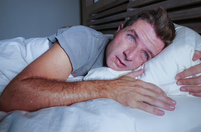 Rusteloze ongerust gemaakte jonge aantrekkelijke mens wakker bij nacht die op bed slapeloos met wijd geopende ogen liggen lijdend stock foto's