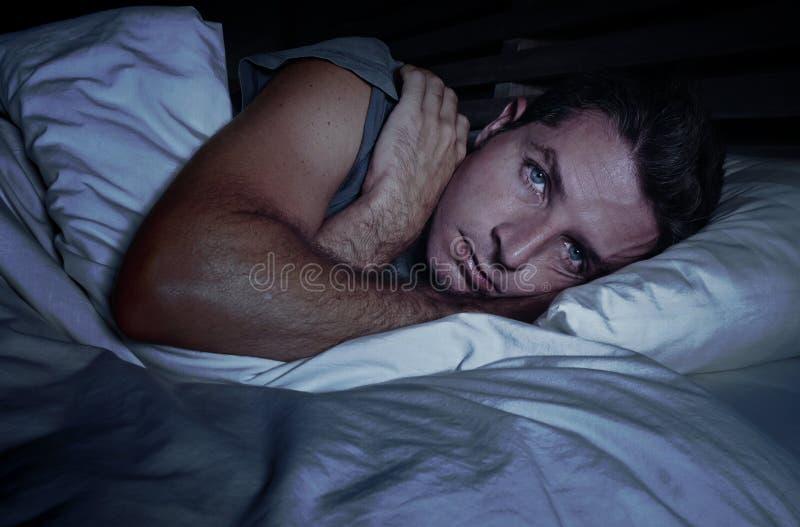 Rusteloze ongerust gemaakte jonge aantrekkelijke mens wakker bij nacht die op bed slapeloos met wijd geopende ogen liggen lijdend stock afbeeldingen