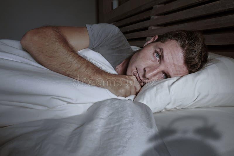 Rusteloze ongerust gemaakte jonge aantrekkelijke mens wakker bij nacht die op slapeloos bed liggen hebbend geopende ogen gedeprim stock afbeeldingen